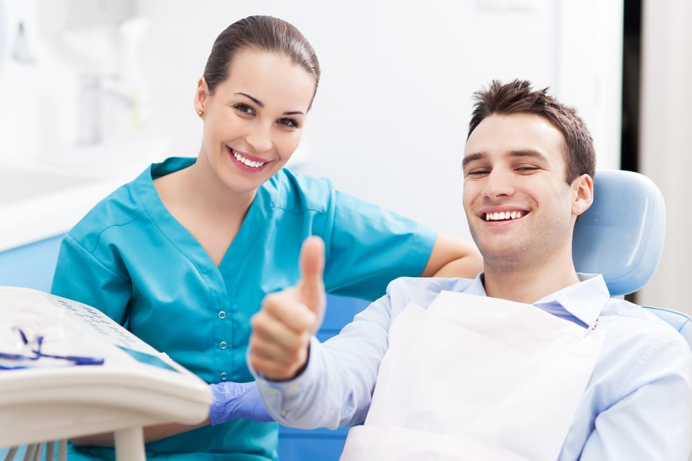 Dentist with happy patient after treating TMJ pain